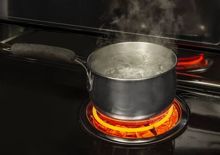 Horizontal shot of a boiling pot of water on a stovetop with a glowing red element with copy space.