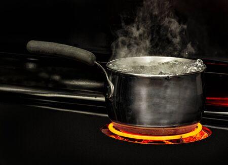Plan horizontal d'une casserole d'eau bouillante sur une cuisinière avec un élément rouge brillant.