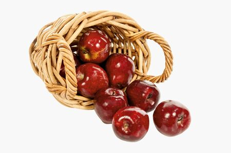 Horizontal shot of a small woven basket with handles on its side with shiny red apples spilling out on a white background. Copy space.