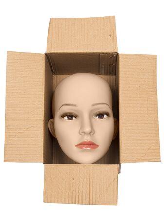 Vertical shot of a bald woman mannequin head inside an open cardboard box. White background.