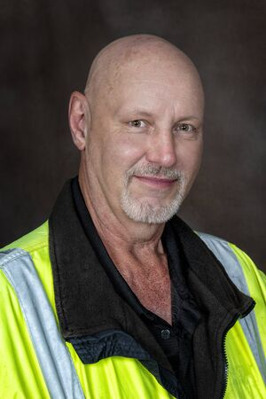 Vertical shot from the chest up of a friendly mature male worker in reflective clothing.  Brown background. Reklamní fotografie