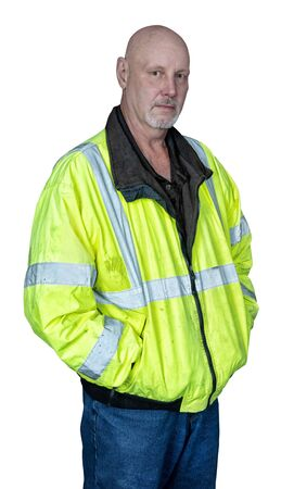 Vertical shot of a mature male worker in a reflective coat on a white background.  He is standing with his hands in his pockets.
