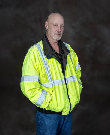 Vertical shot of a mature male worker in a reflective coat on a brown background.  He is standing with his hands in his pockets. Reklamní fotografie