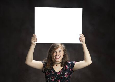 Horizontal studio shot of a happy pre-teen girl with freckles holding a blank white sign on her head on a brown background.