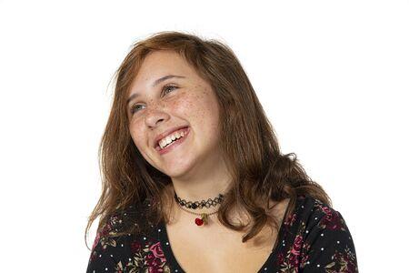 Disparo de estudio horizontal de una niña preadolescente riendo con pecas aislado en blanco con espacio de copia. Disparo desde el pecho hacia arriba.