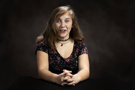 Horizontal studio shot of a surprised and amused pre-teen girl.  Brown background.  She is sitting down.  Shot is from the waist up. Imagens