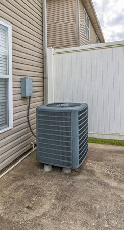 Vertical shot of an air conditioning unit on the patio behind a condo.