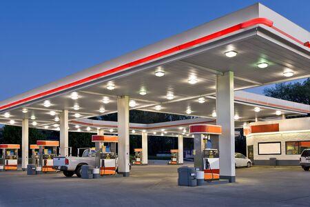 Horizontale opname van een tankstation en een supermarkt in de schemering.