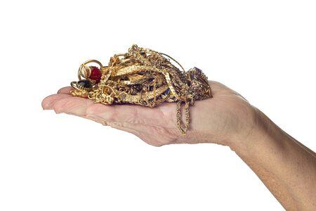 Disparo horizontal de la mano de una mujer sosteniendo un montón de joyas de oro. Aislado en blanco.