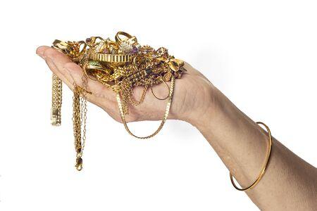 Disparo horizontal de la mano y el brazo de una mujer sosteniendo un montón de bisutería de oro y con un brazalete. Fondo blanco con espacio de copia. Foto de archivo