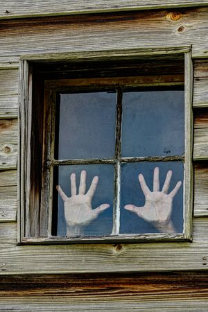 Vertical shot of a four paned window in a wooden wall with a woman's hands pressed against two of the panea as if trying to escape.