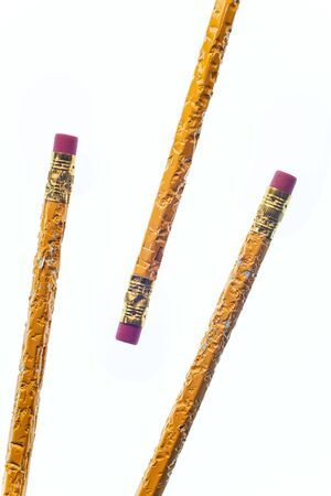 Vertical shot of the eraser end of three chewed pencils. Two are coming from the bottom left corner and the other pencil from the upper right corner.  White background.  Copy Space.