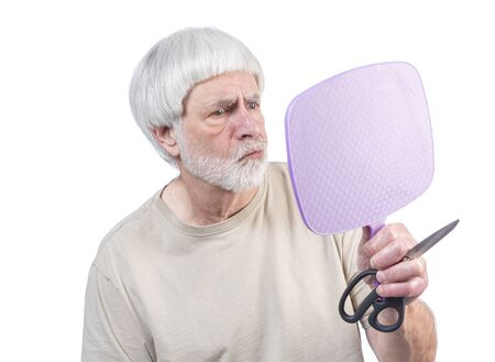 Horizontal shot of a gray haired man who's been in quarantine too long looking at the haircut he just gave himself and is unsure about the results.