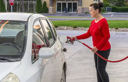Horizontal shot of a middle-aged woman pumping gas into her white car.