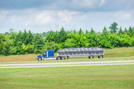 Horizontal shot of a blue 18-wheeler with a covered bed traveling down a Tennessee highway. Stock Photo