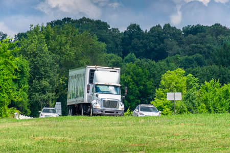 Traffic in Tennessee on a hot day. Shimmering waves of heat from the pavement adds an interesting texture to the vehicles and trees behind them.