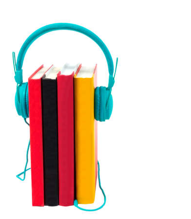 Vertical shot of four colorful books standing on end with a pair of turquoise headphones plugged into them.