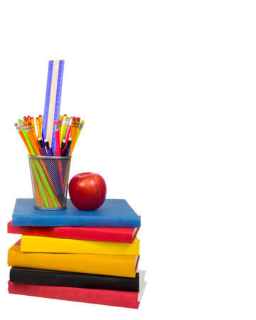 Vertical shot of a stack of colorful books with an apple and a wire pencil holder sitting on top. Pencil holder is holding pencils and a ruler. Isolated on white. Copy space on the right side and the top.