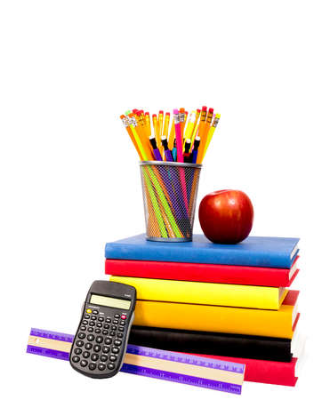 Vertical shot of new school supplies: colorful books, ruler, calculator, pencils in holder, and an apple.
