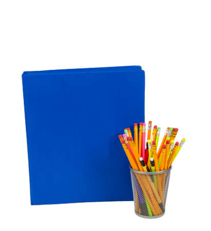 Blue notebook with lots of copy space and colorful pencils in a pencil holder. Isolated on white.