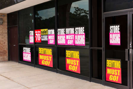 Horizontal angled shot of the windows of a store plastered with going out of business signs due to the pandemic.