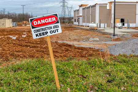 Horizontal shot of a Danger Construction Area Keep Out sign next to a fast food restaurant under construction.