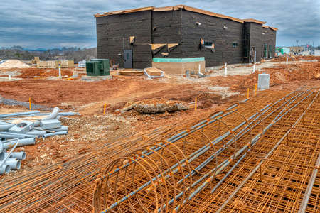 Horizontal shot of metal reinforcements lying in the foreground of a new commercial construction site.