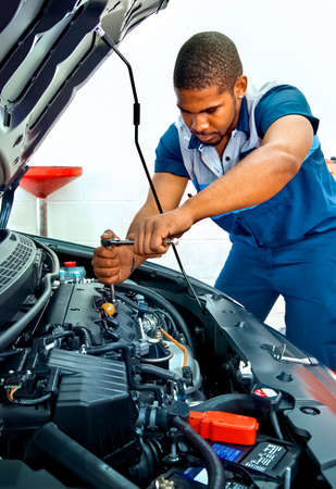 Horizontal shot of an automotive technician working on a car engine. This is a revised picture. Banco de Imagens