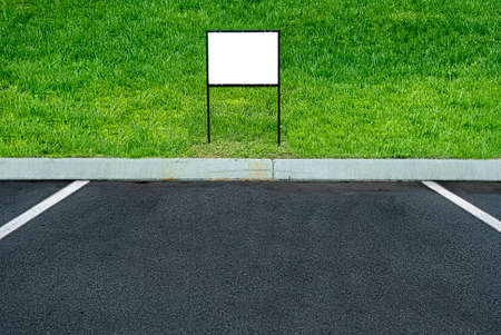 Horizontal shot of a blank sign at the end of a parking space with green grass behind it. This is a revised image.