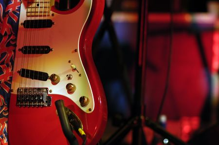 pickups: Classic red electric guitar in shaft of white stage lighting.