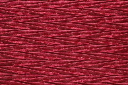 zag: Close-up of deep red textured fabric.