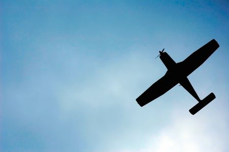 light aircraft silhouette on cloudy sky