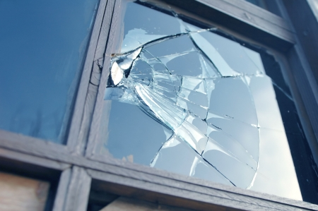 smashed window reflecting blue sky Stock Photo