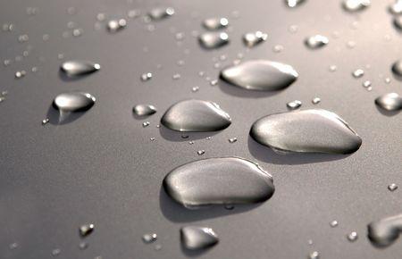 waxed: raindrop close-up on luxury metallic vehicle panel