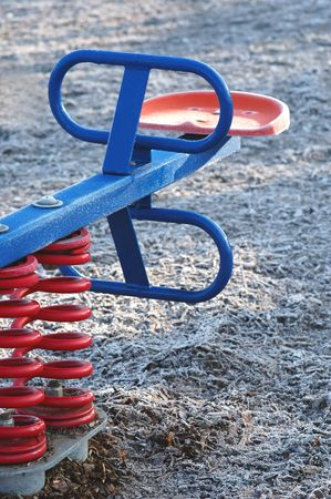 sprung: modern see-saw in a frosty childrens playground