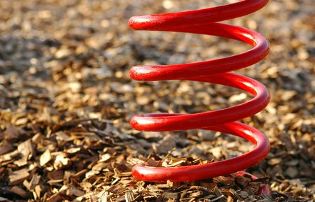 twisty: abstract of a big red spring on a wood chip base Stock Photo