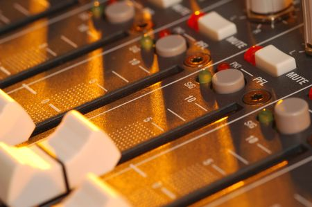 across: golden light falling across mixing soundboard