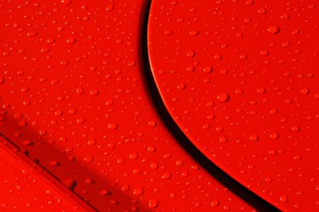 background of raindrops on a red sports car panel photo