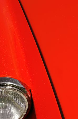red sports car hood with some raindrops on panels photo