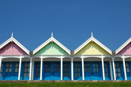 pastel beach huts against a clear blue sky