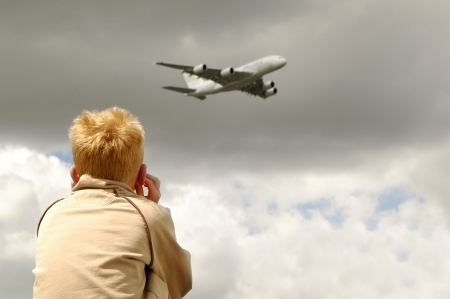 noisy: child protects ears from the noise of low flying jet
