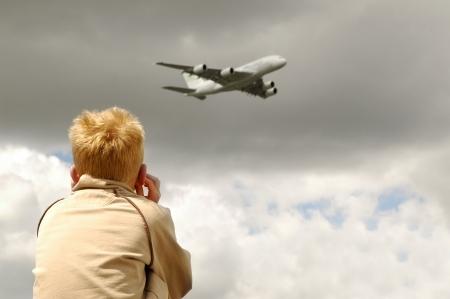 niño protege los oídos del ruido del chorro de vuelo bajo