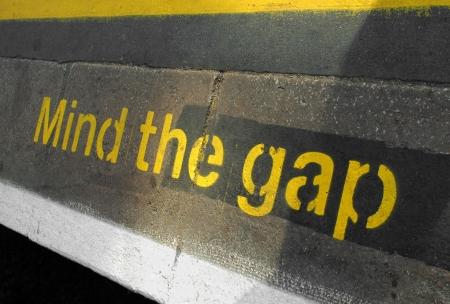 mind the gap sign on a railway or subway platform photo