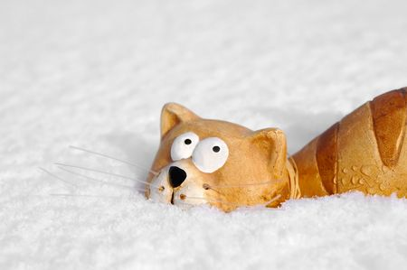 ceramic toy cat sinking into snow photo