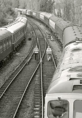 diesel locomotives: two distant workers walking on railroad tracks