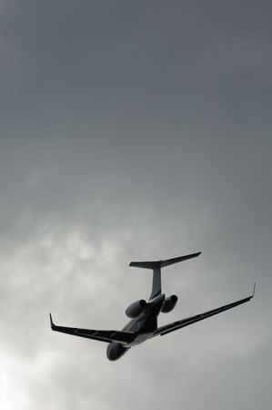 business jet taking off into a stormy gray sky photo
