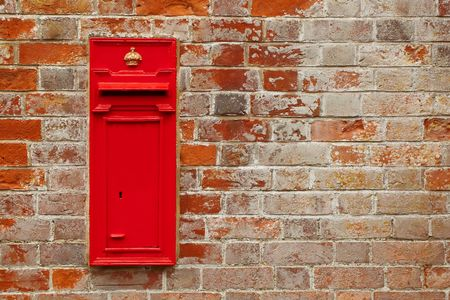 letterbox: traditional british postal box against a red brick wall Stock Photo