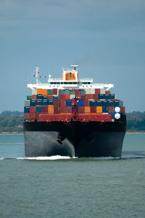 hull: fully loaded container ship head-on in calm water Stock Photo