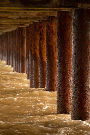 metal pillars under the boardwalk of a seaside pier photo