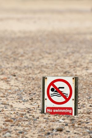 no swimming: no swimming sign on a pebbled beach Stock Photo